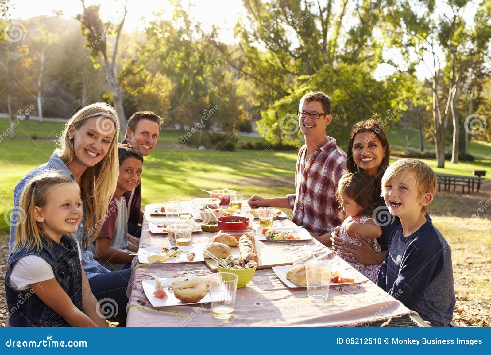 Duas famílias que têm um piquenique em um olhar da tabela à câmera