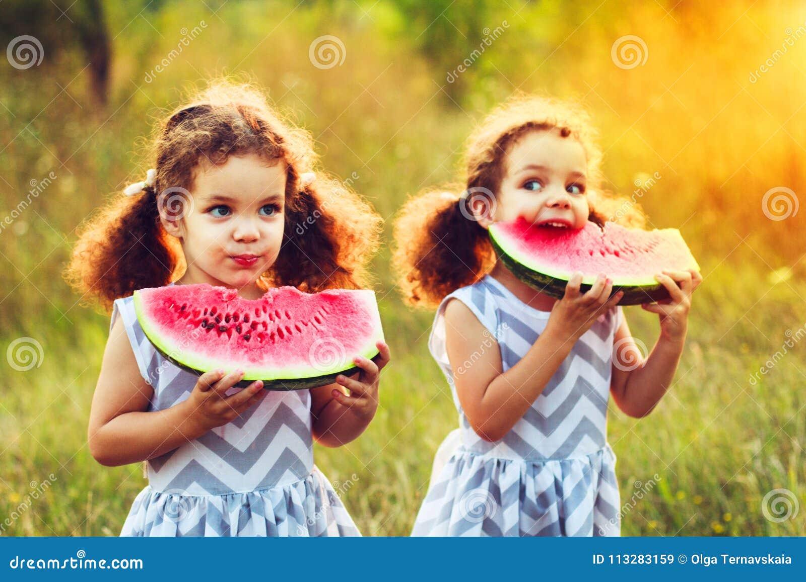 Duas irmãs mais nova engraçadas que comem a melancia fora no dia de verão morno e ensolarado Alimento biológico saudável para cri
