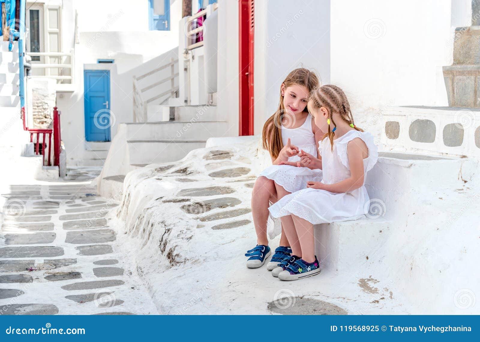 Duas irmãs que sentam-se nas escadas na rua grega