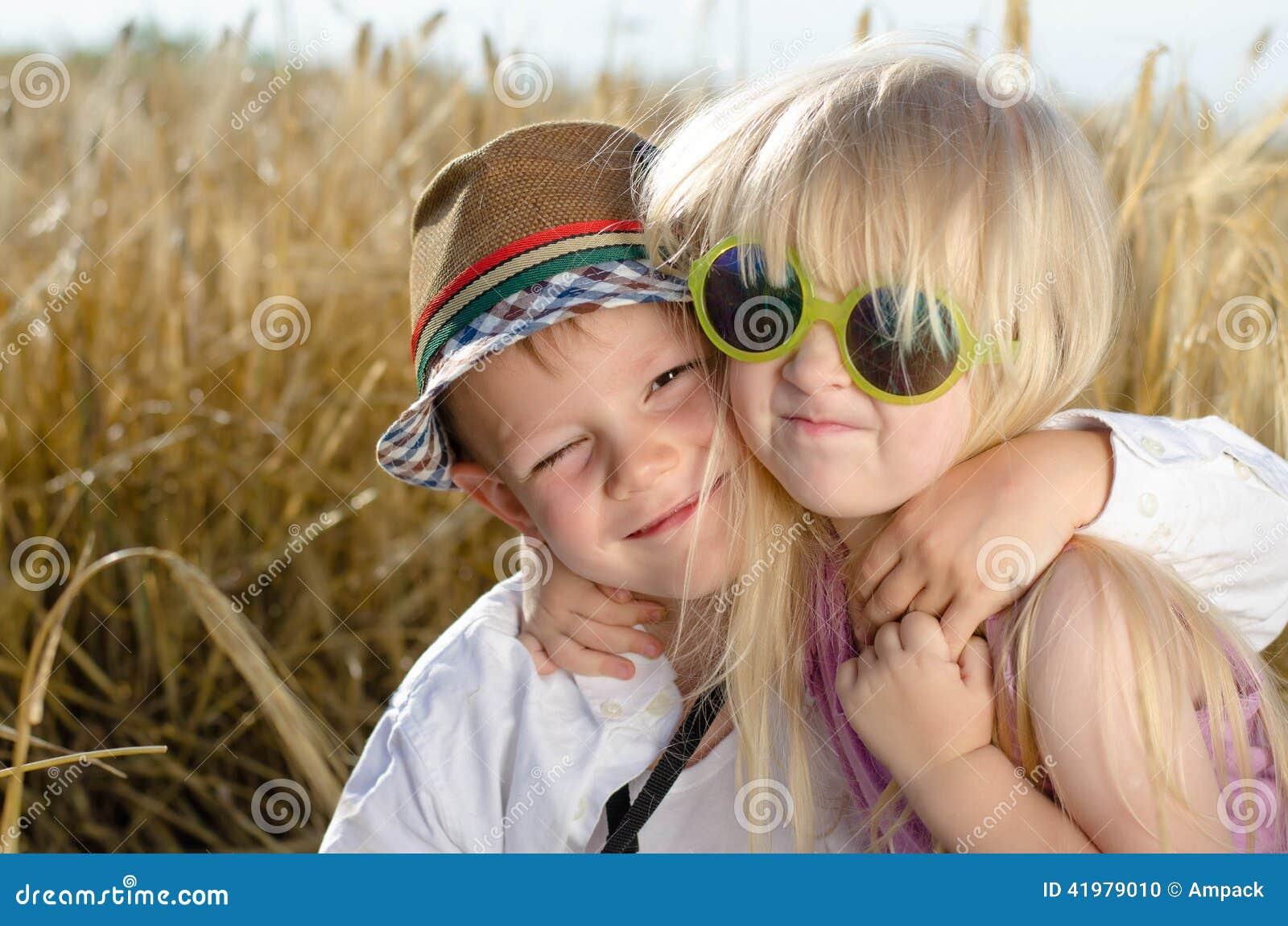 Dois irmãos de sorriso felizes engraçados louros bonitos