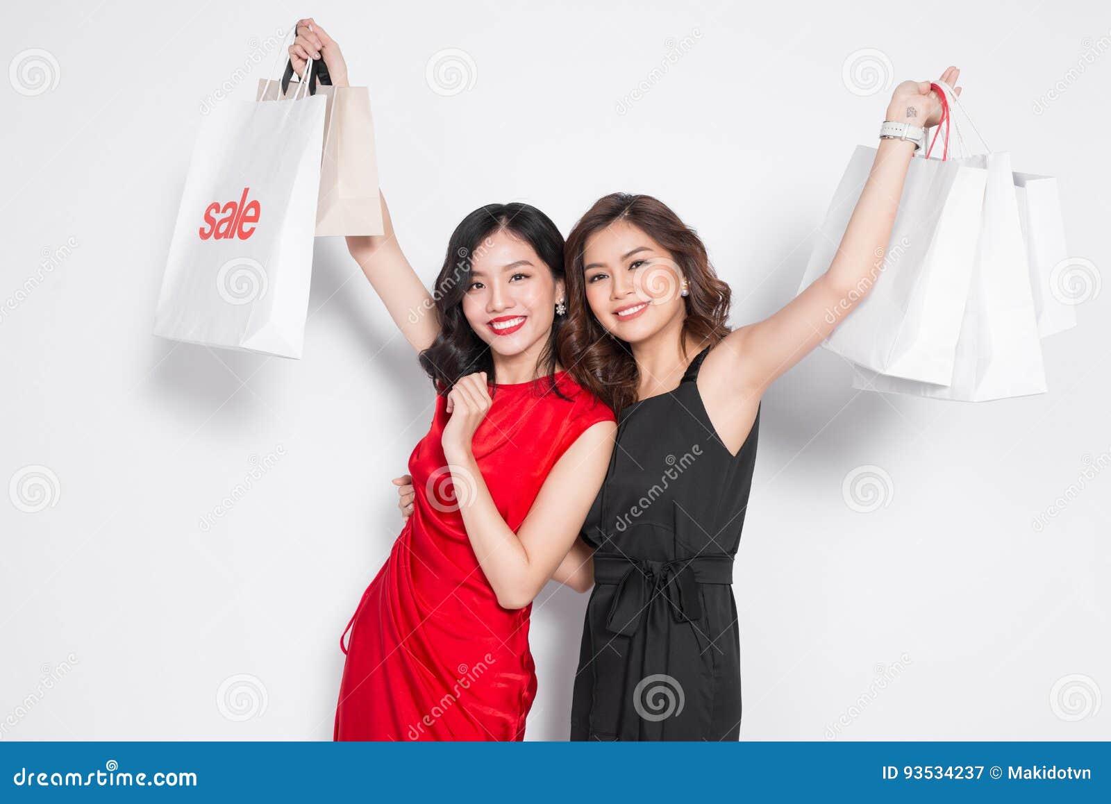 Duas jovens mulheres atrativas felizes com os sacos de compras no CCB branco