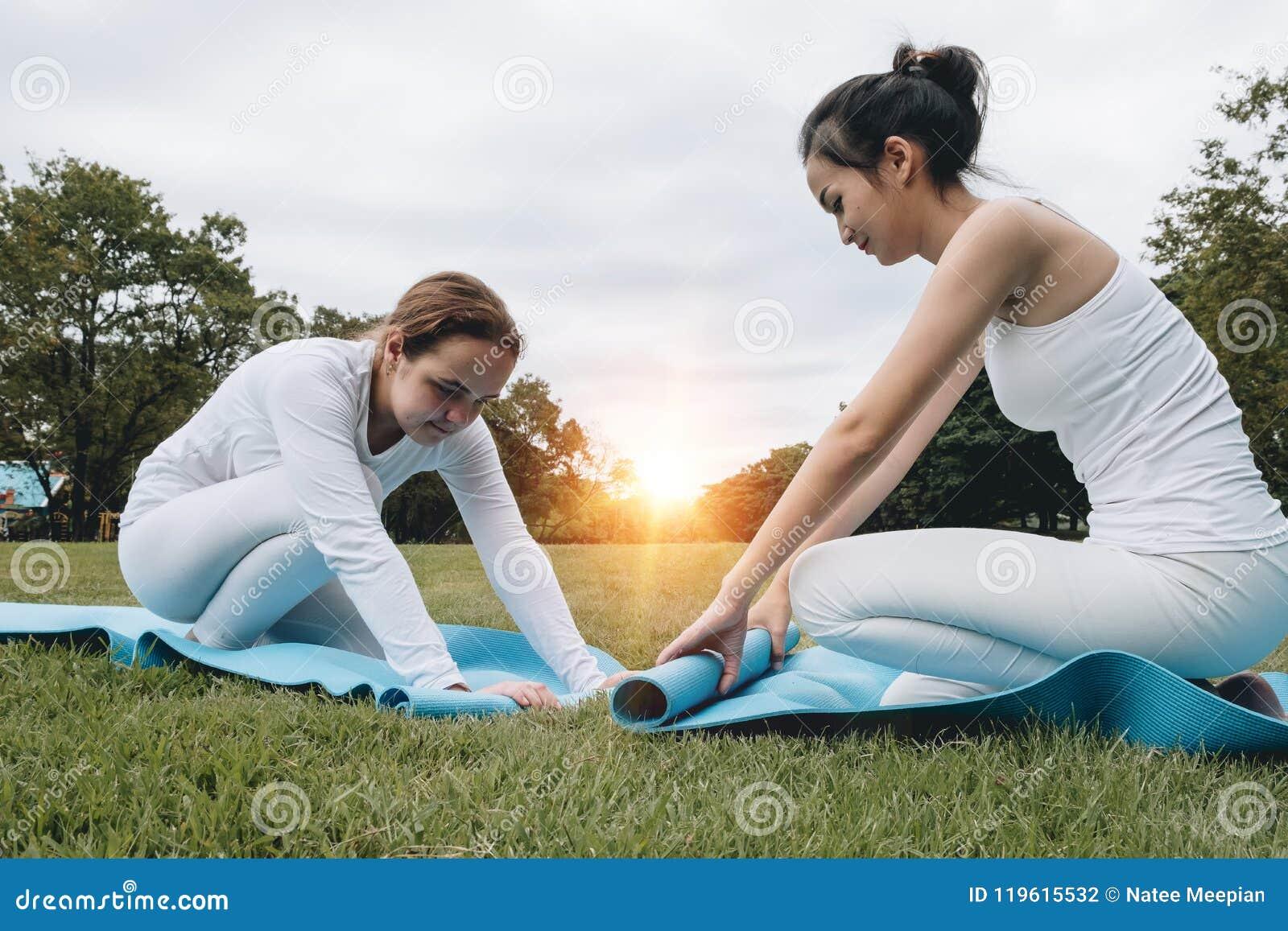 Duas jovens mulheres atrativas que dobram o afte azul da esteira da ioga ou da aptidão