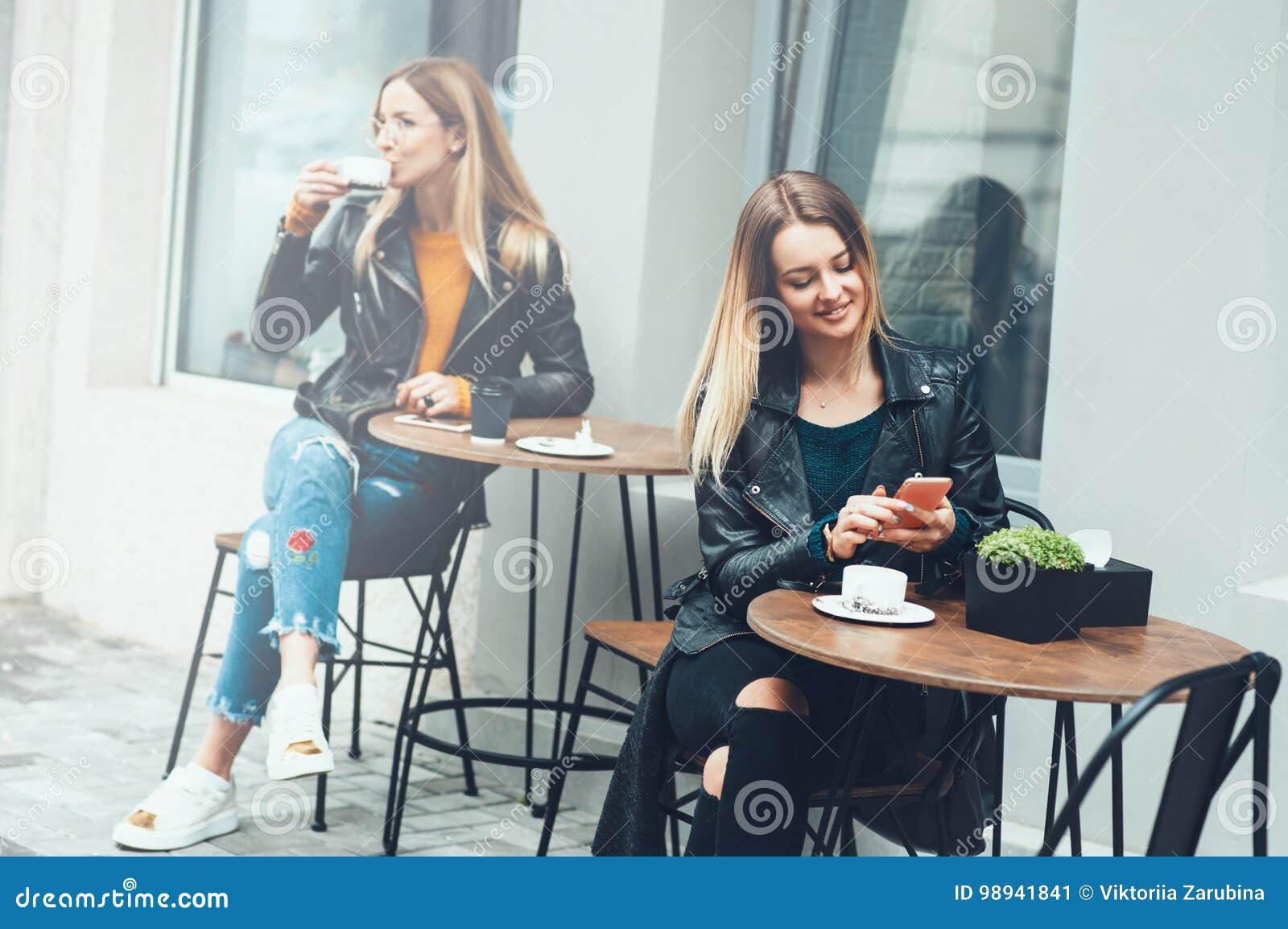 Duas jovens mulheres bonitas em elegante vestem o assento exterior no café e a utilização de smartphones ao beber o café Messa do