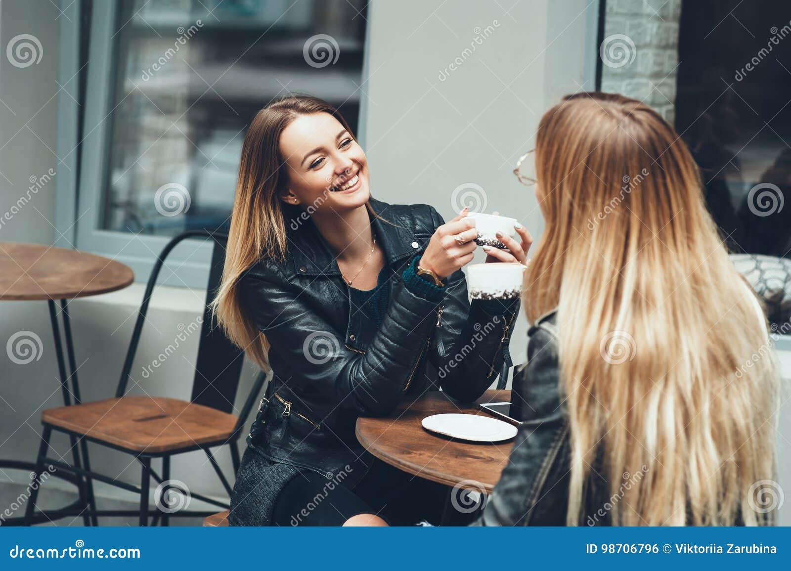 Duas jovens mulheres bonitas na roupa da forma que tem o resto que falam e café bebendo no restaurante exterior