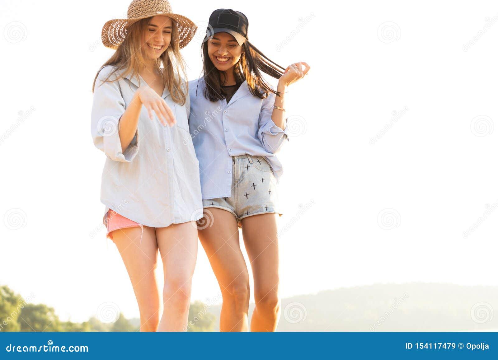 Duas jovens mulheres bonitas que d?o uma volta em uma praia Amigos f?meas que andam na praia e que riem em um dia de ver?o