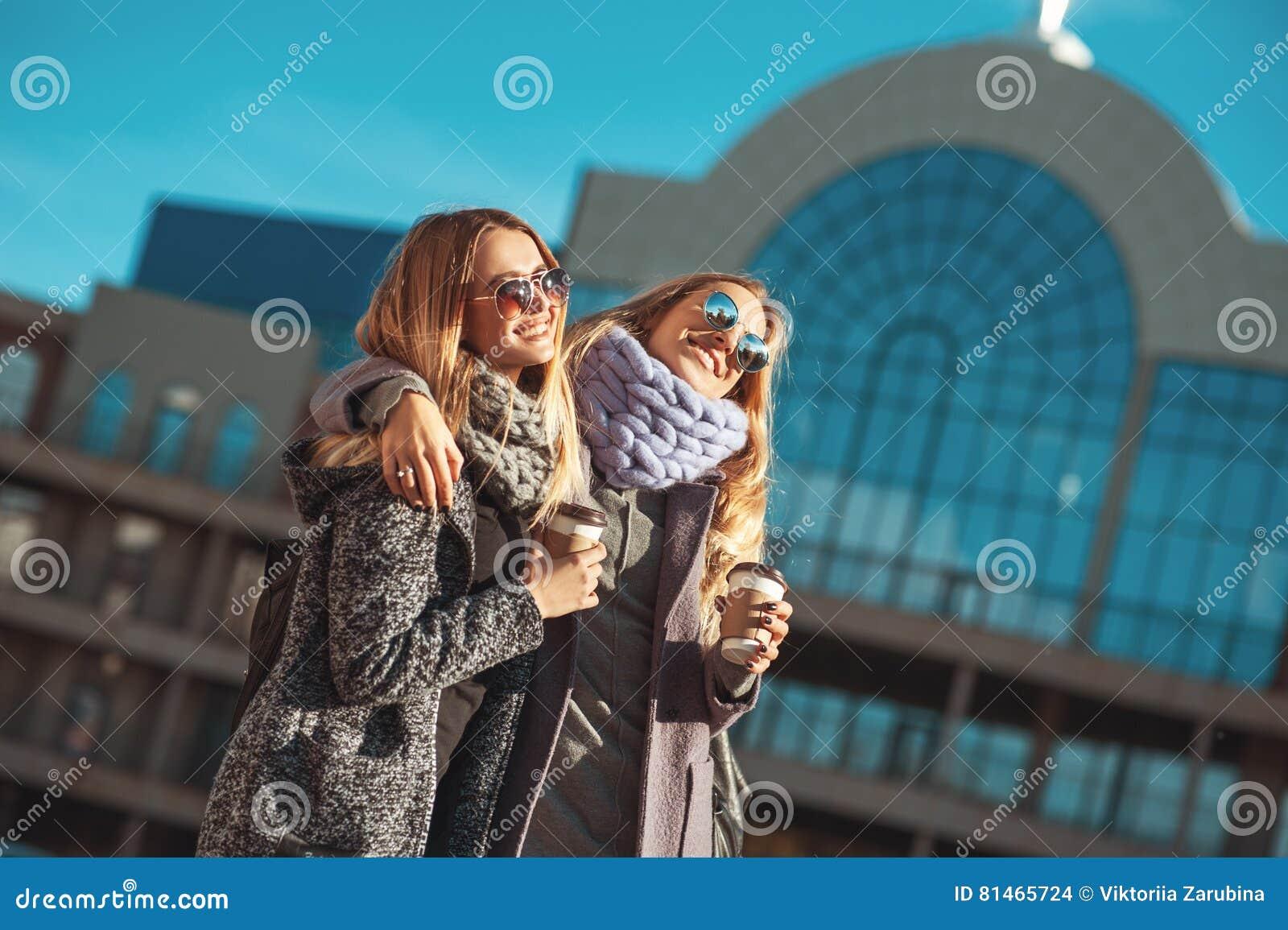 Duas jovens mulheres bonitas que falam ao andar a rua após a compra guardando o café e o sorriso