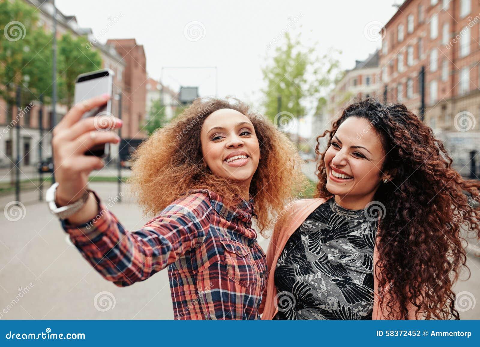 Duas jovens mulheres bonitas que tomam uma imagem junto
