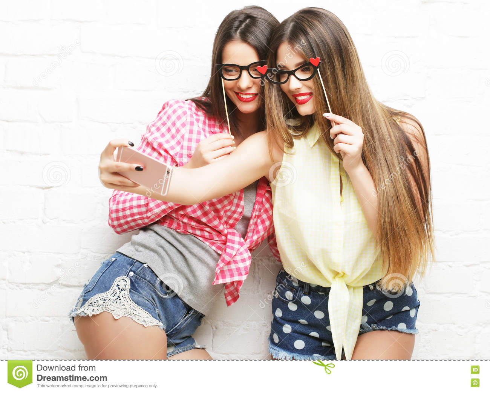 Duas jovens mulheres com os vidros do partido que tomam o selfie