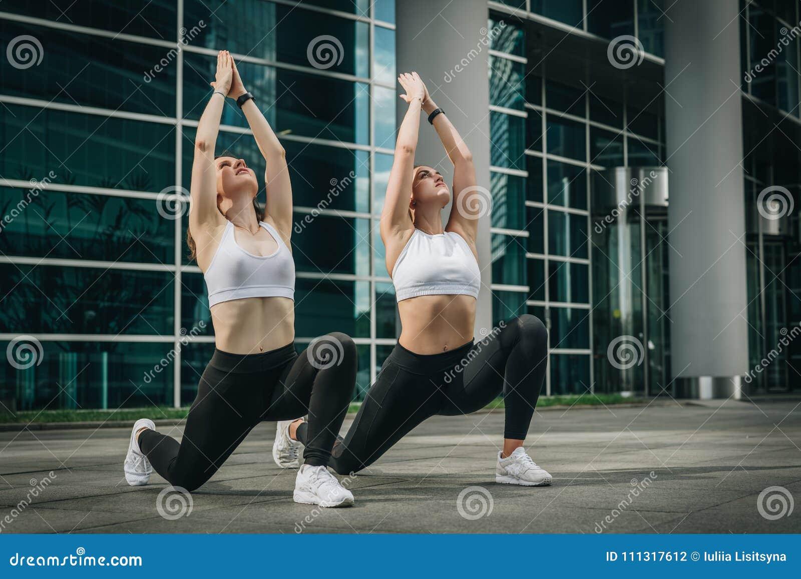 Duas jovens mulheres, meninas que fazem esticando exercícios, aquecem-se, fazendo a ioga na rua da cidade Exercício, deitando na
