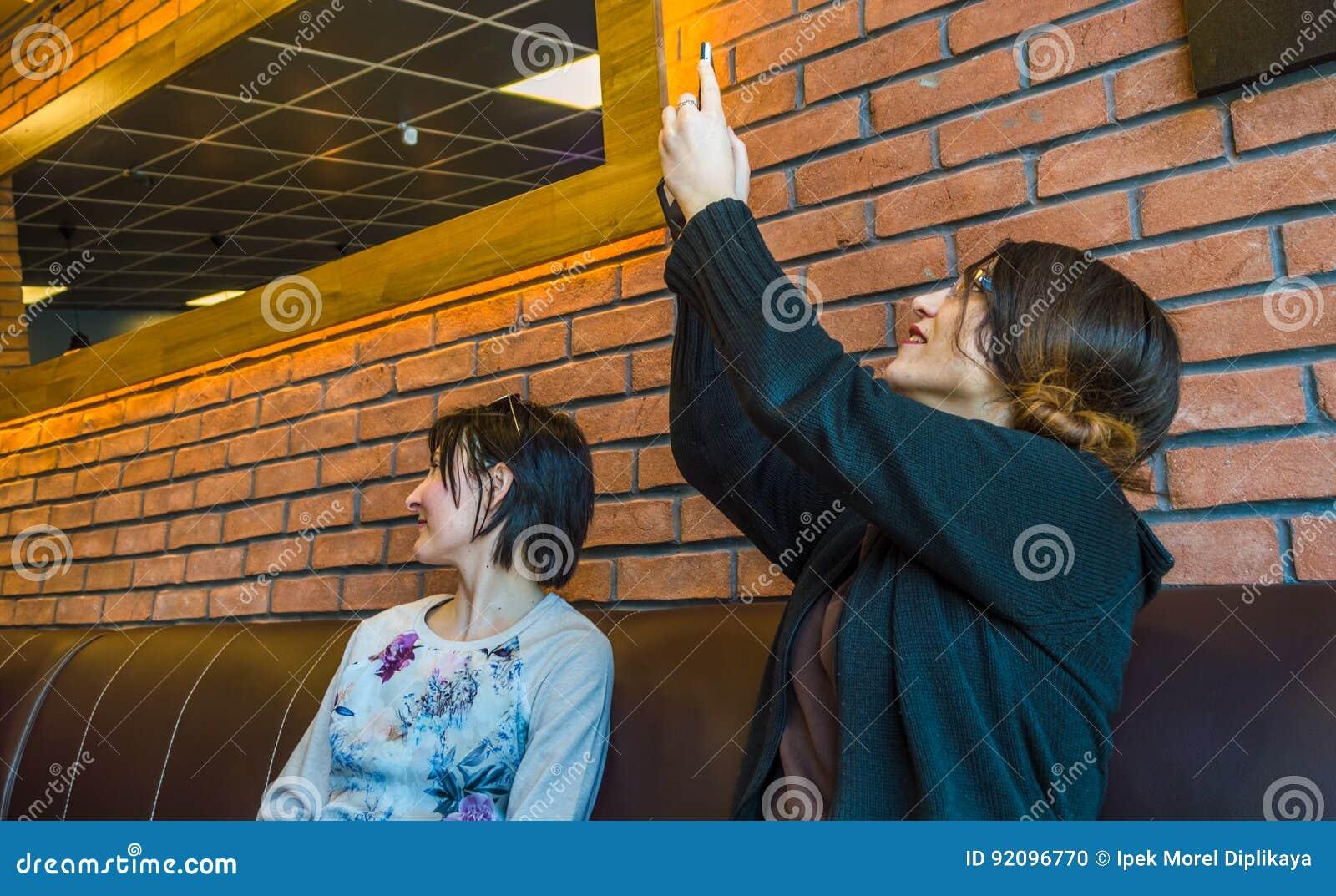 Duas jovens mulheres morenos que sentam-se em um café junto