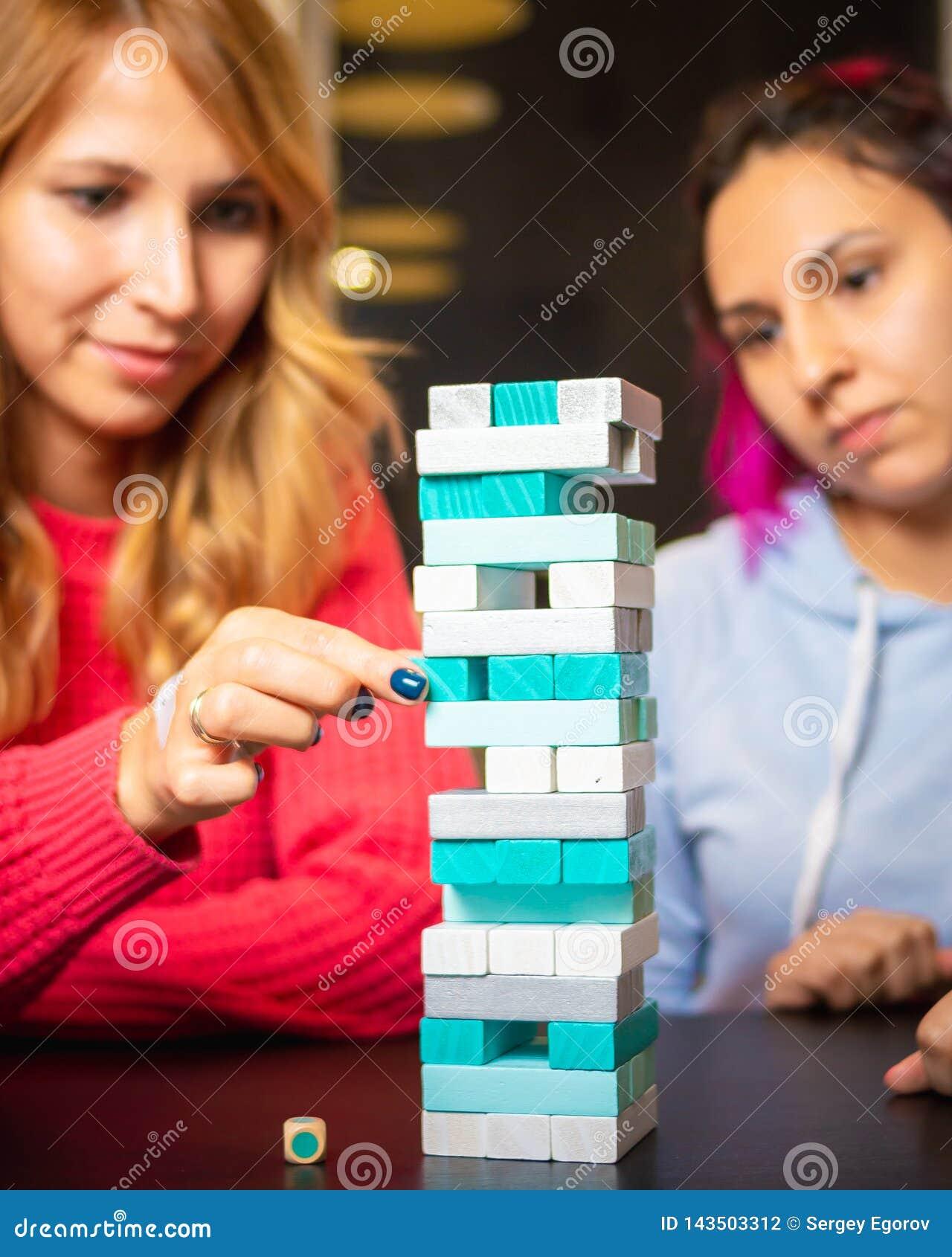 Duas jovens mulheres que jogam o jenga colorido