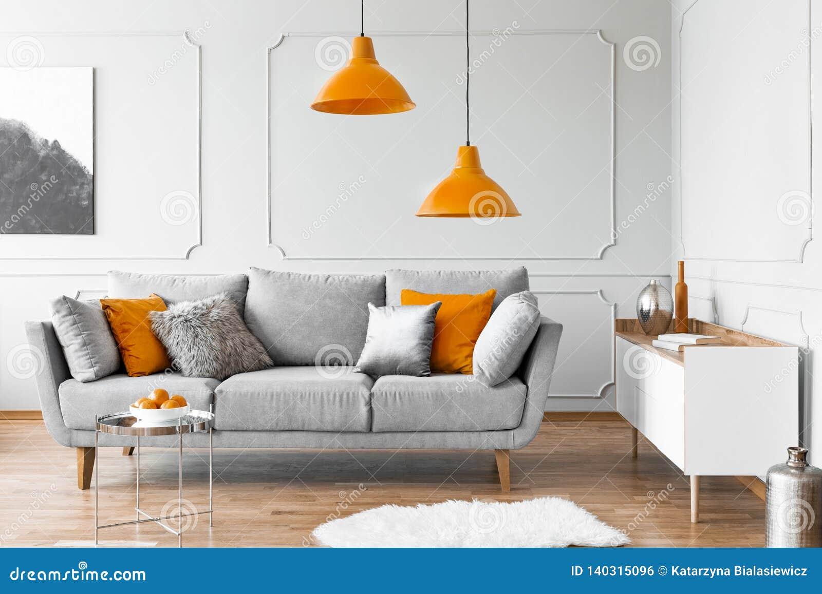 Duas lâmpadas alaranjadas acima do sofá escandinavo cinzento com descansos