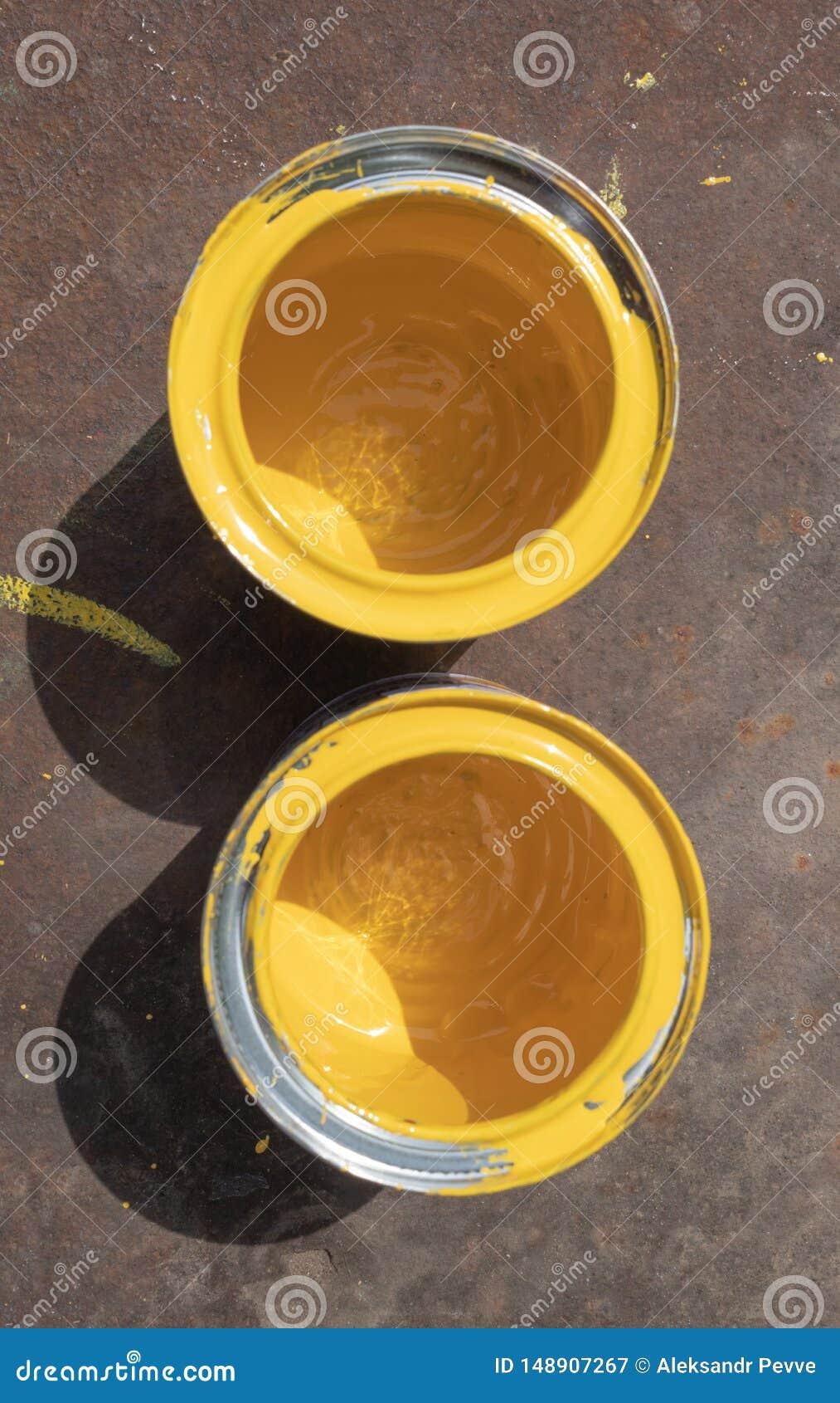 Duas latas amarelas vazias da pintura com borr?es est?o em uma folha oxidada do ferro iluminada pela luz solar