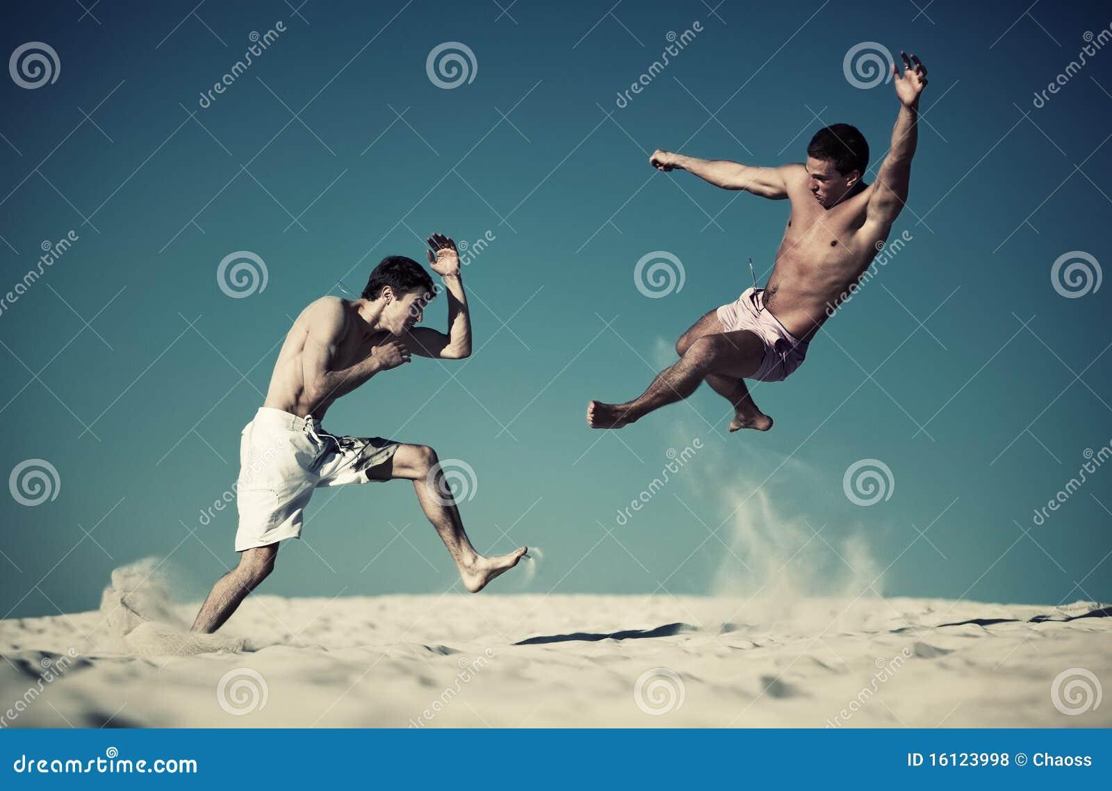 Duas lutas do esporte dos homens novos na praia