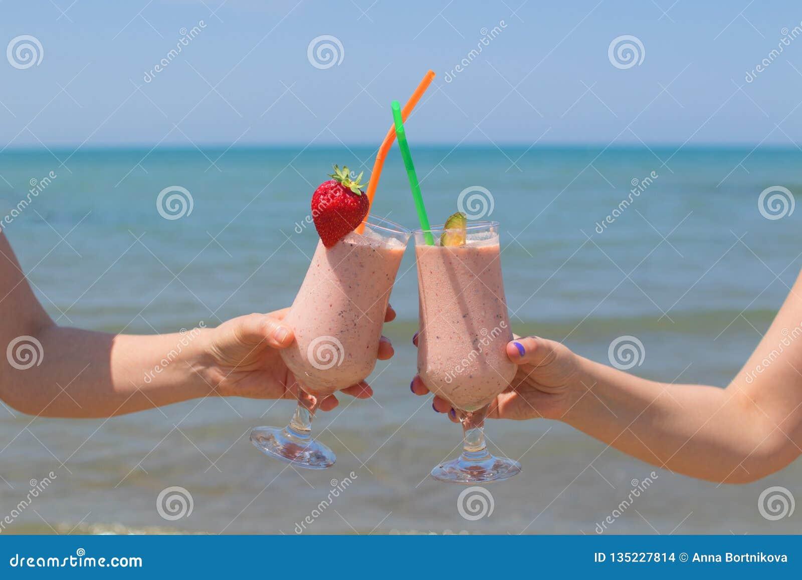 Duas mãos fêmeas estão guardando milks shake da morango no fundo do mar