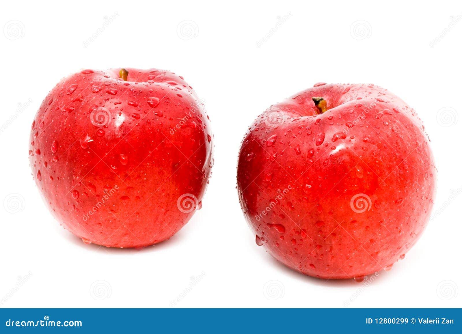 Duas maçãs vermelhas estão nas gotas da água