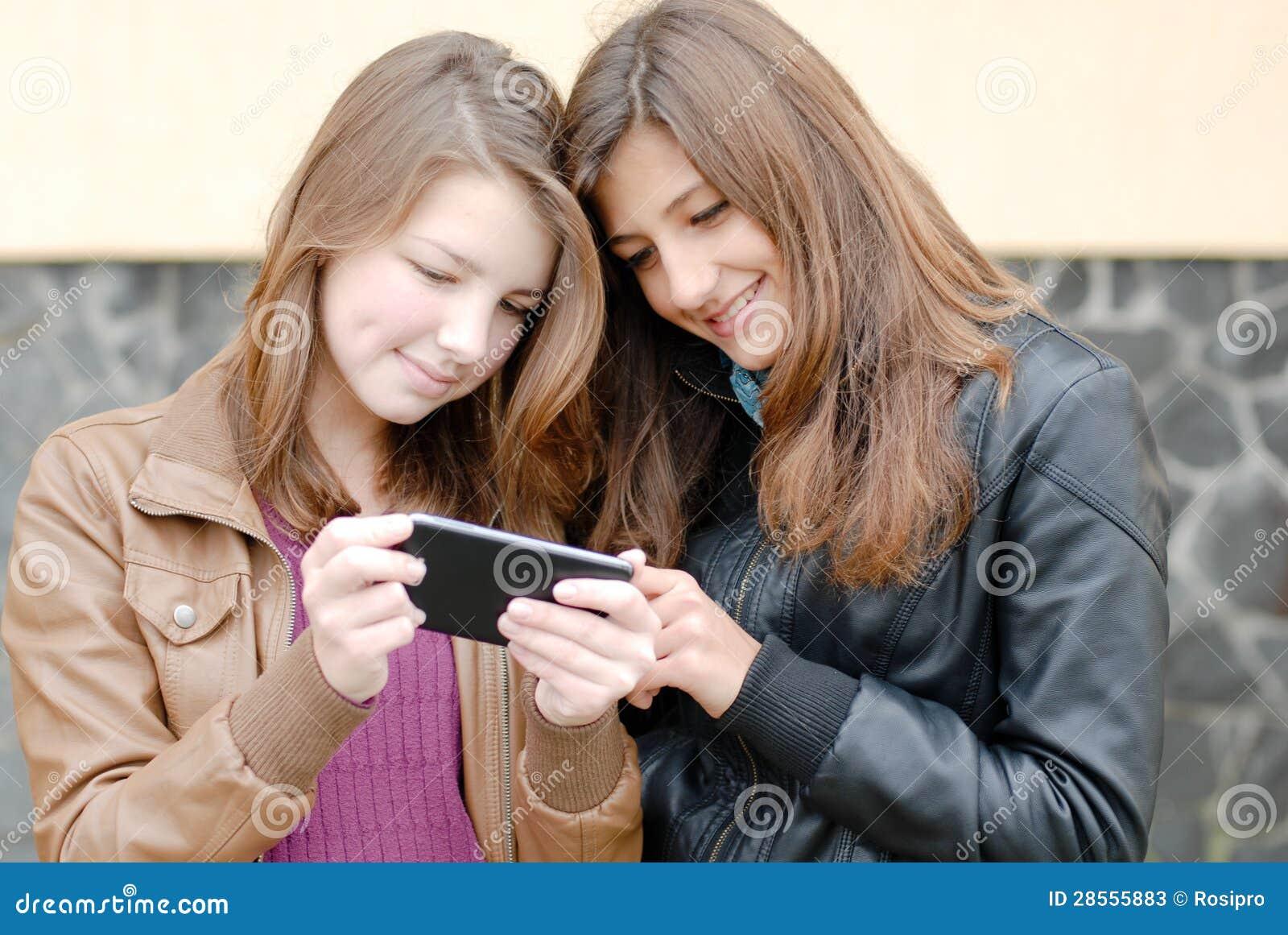 1f8abf8ff79 Duas Meninas Adolescentes Que Olham No PC Da Tabuleta Imagem de ...