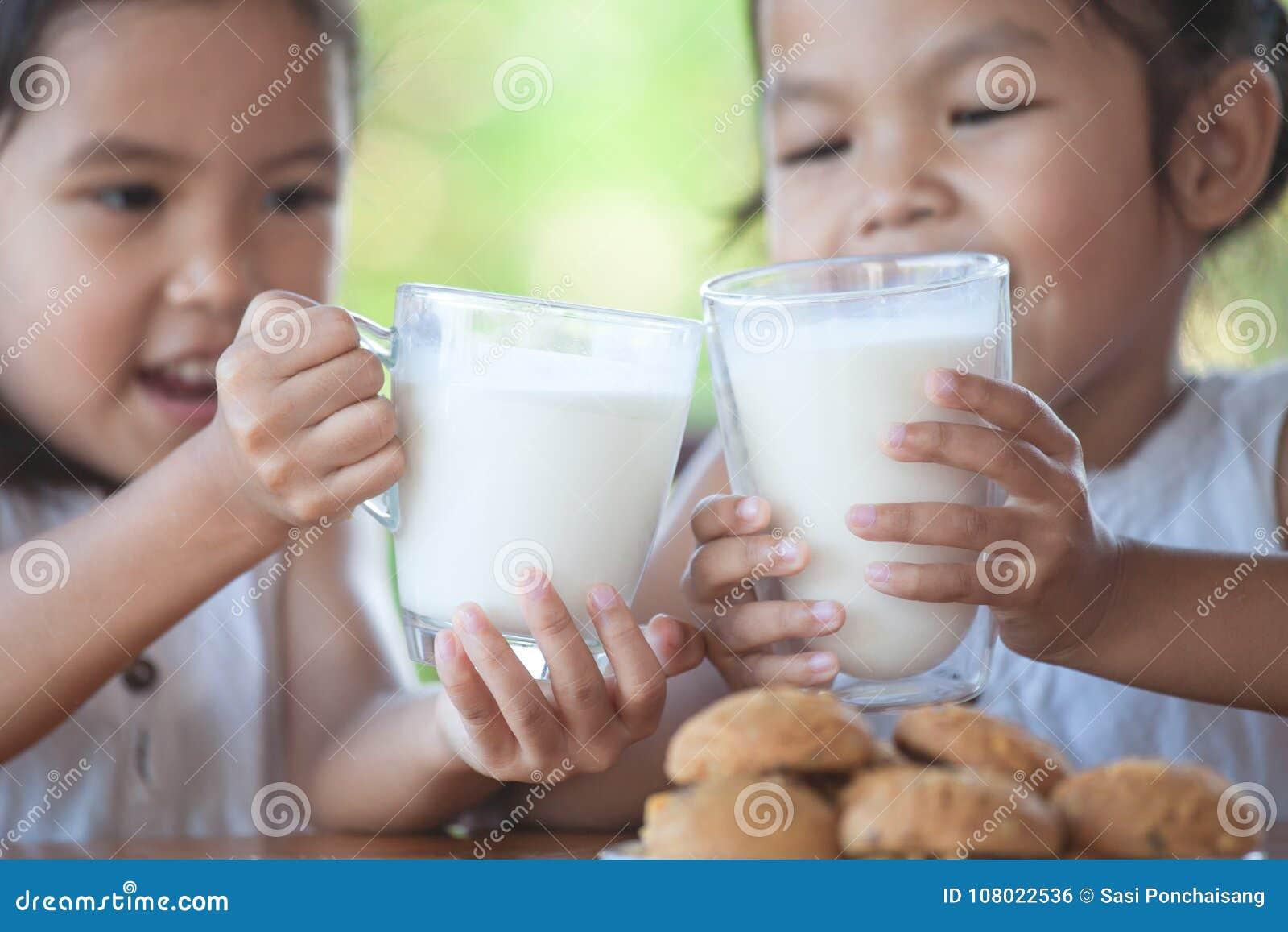 Duas meninas asiáticas bonitos da criança pequena que guardam o vidro do leite
