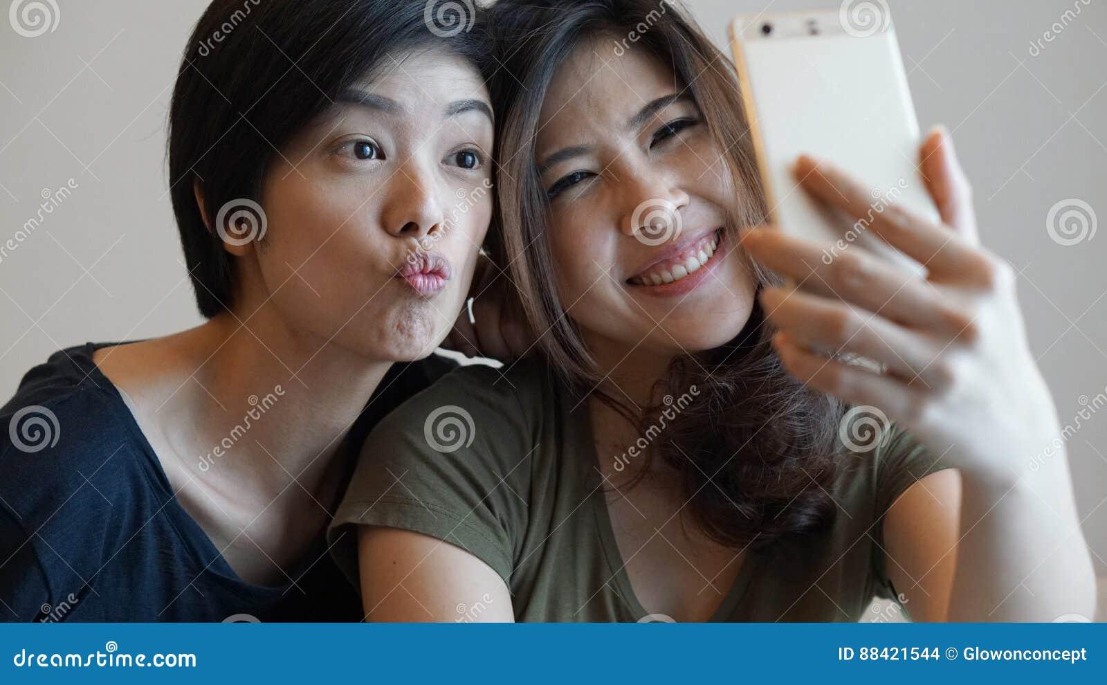 Duas meninas asiáticas da raça misturada que tomam o selfie com telefone esperto
