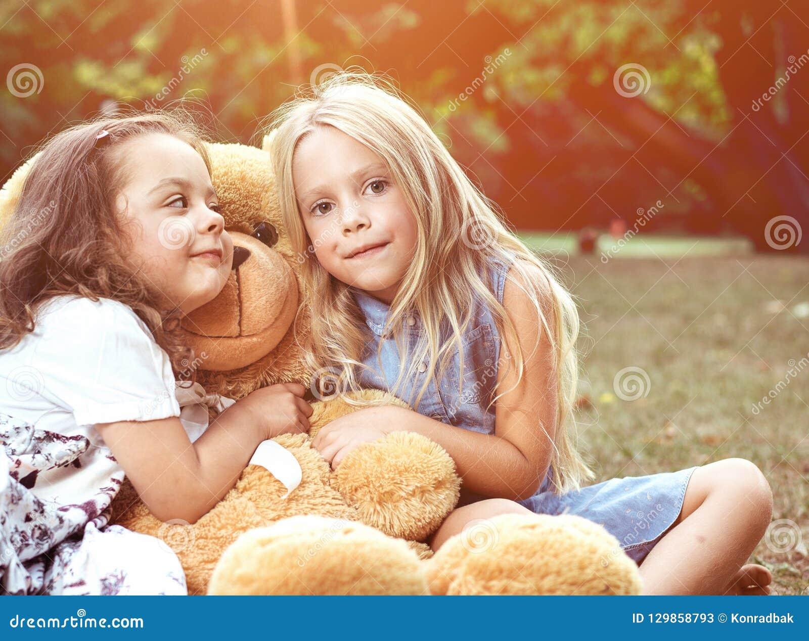 Duas meninas bonitos que abraçam um urso de peluche enorme