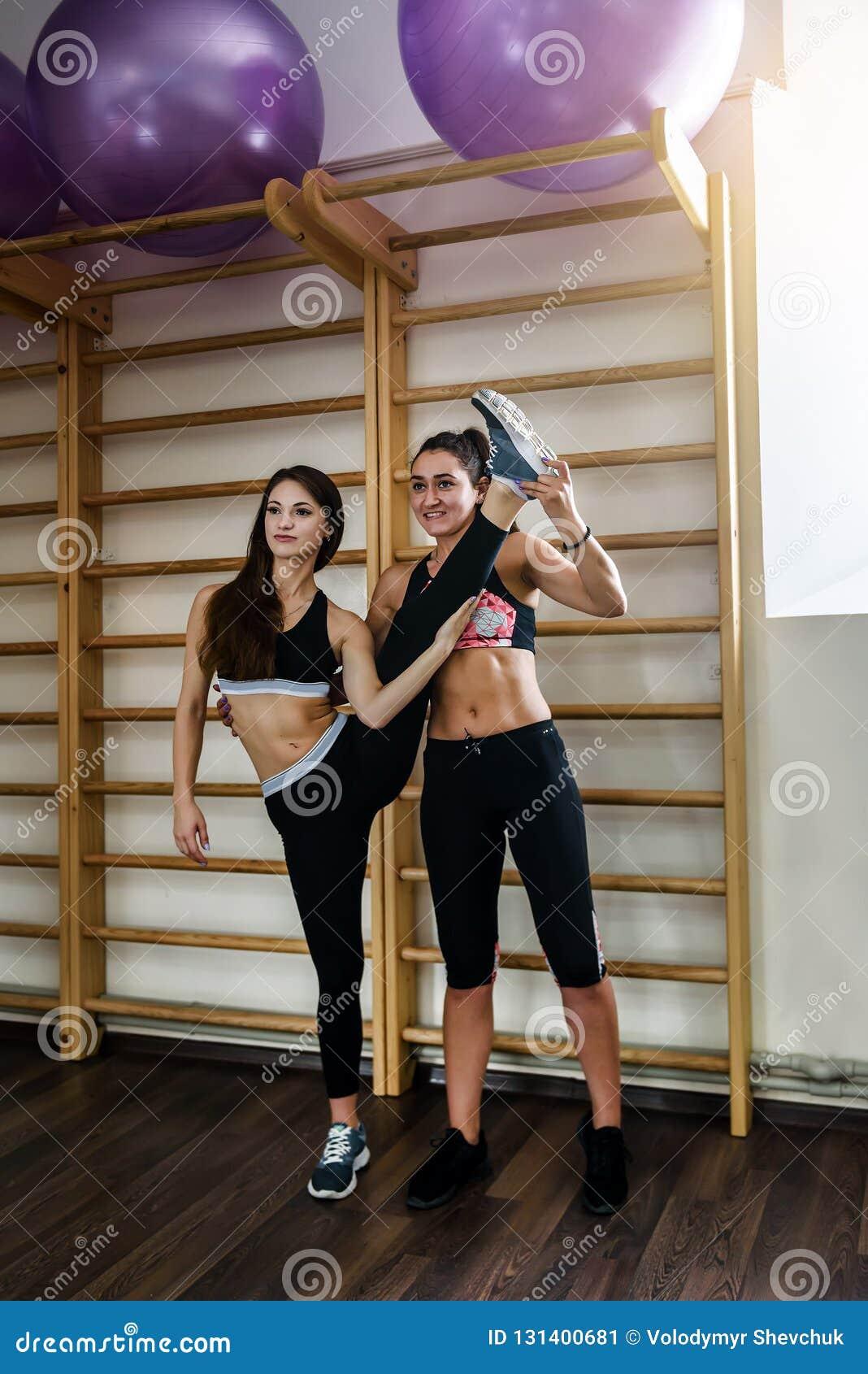 Duas meninas estão fazendo a ioga, ginástica aeróbica, exercícios dos pilates