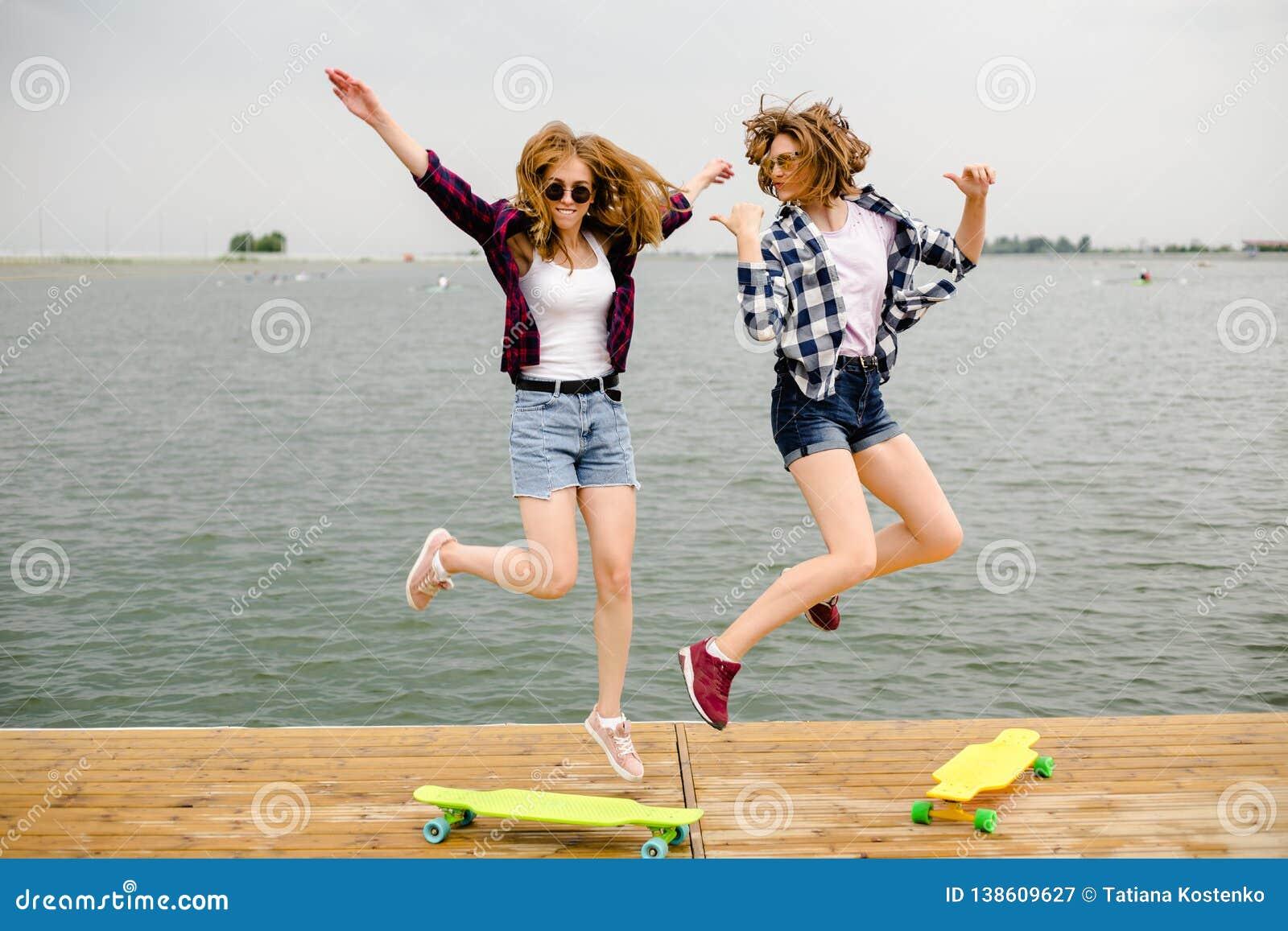 Duas meninas felizes alegres do skater no equipamento do moderno que tem o divertimento em um cais de madeira durante férias de v