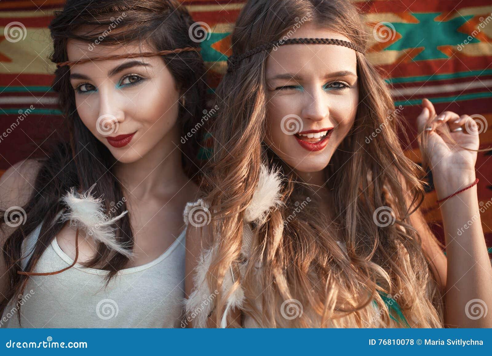 Duas meninas felizes bonitas que enviam o beijo e a piscadela sobre a parte traseira ecthic