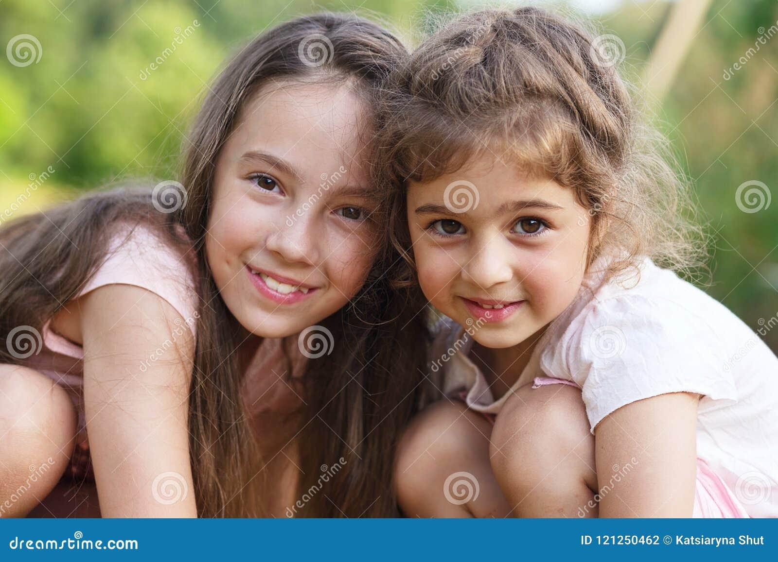 Duas meninas felizes que abraçam no parque do verão