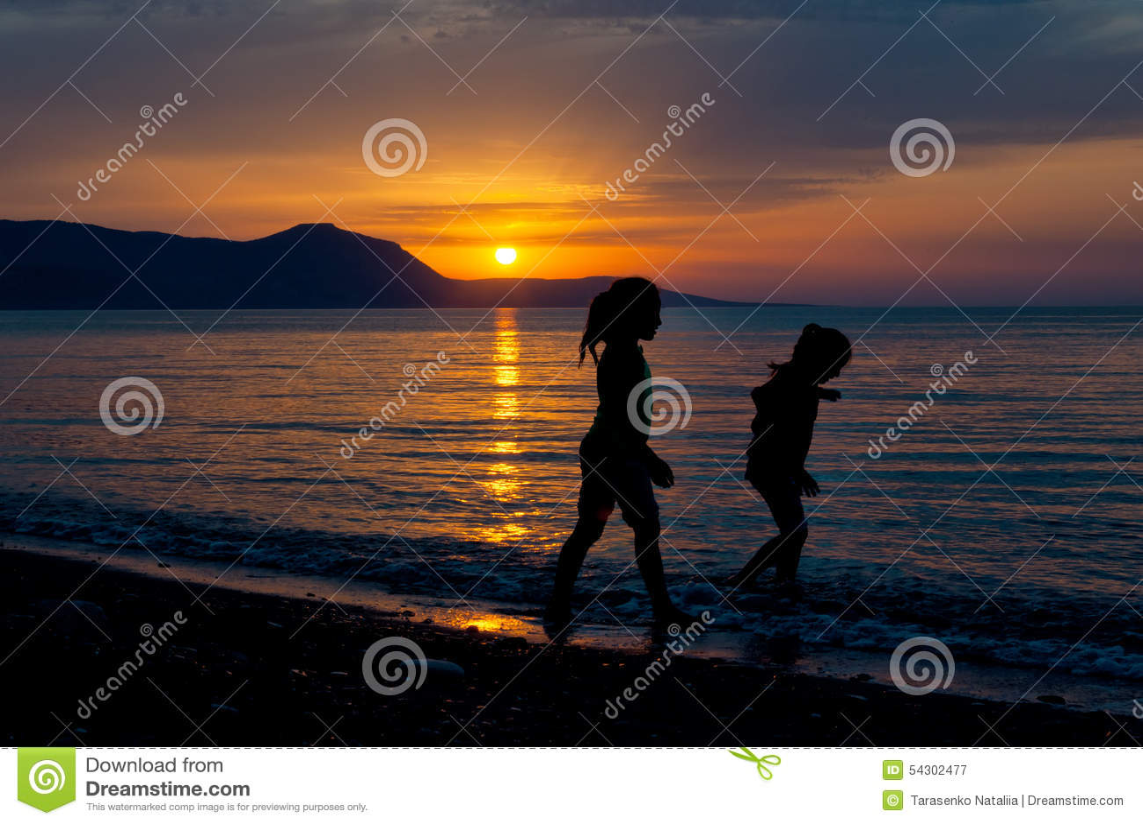 Duas meninas que andam ao longo da praia durante o por do sol