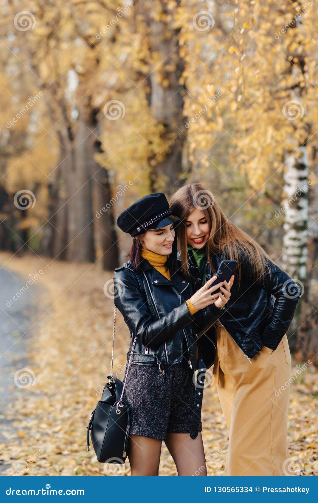 Duas moças acolhedores andam na estrada do parque do outono para fazer fotos