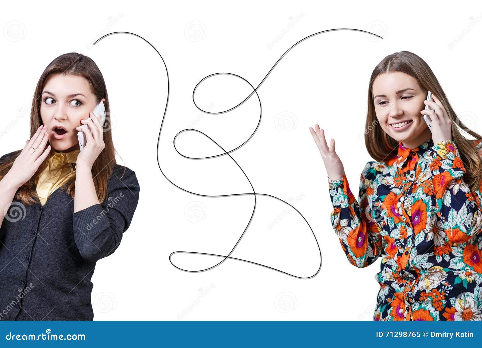 Duas moças que falam por telefones celulares