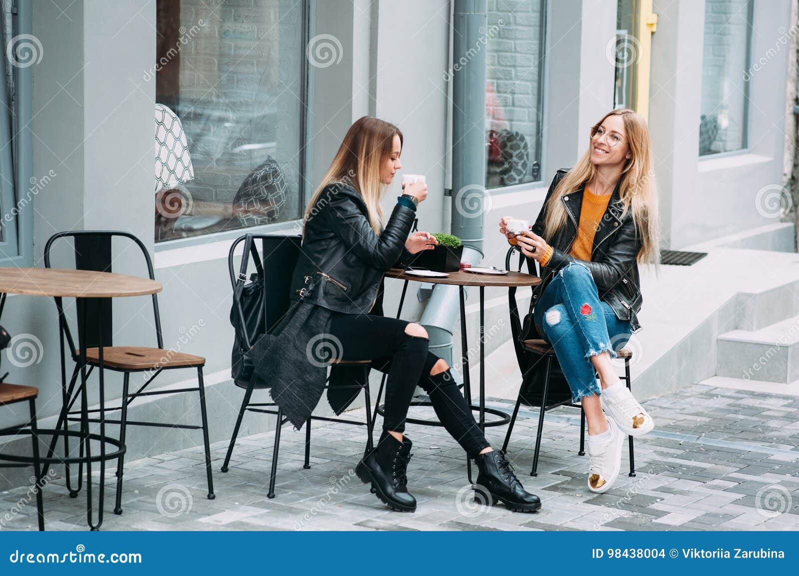 Duas mulheres à moda atrativas bonitas são assento exterior no coffe bebendo do café e chá que falam e que apreciam o grande dia