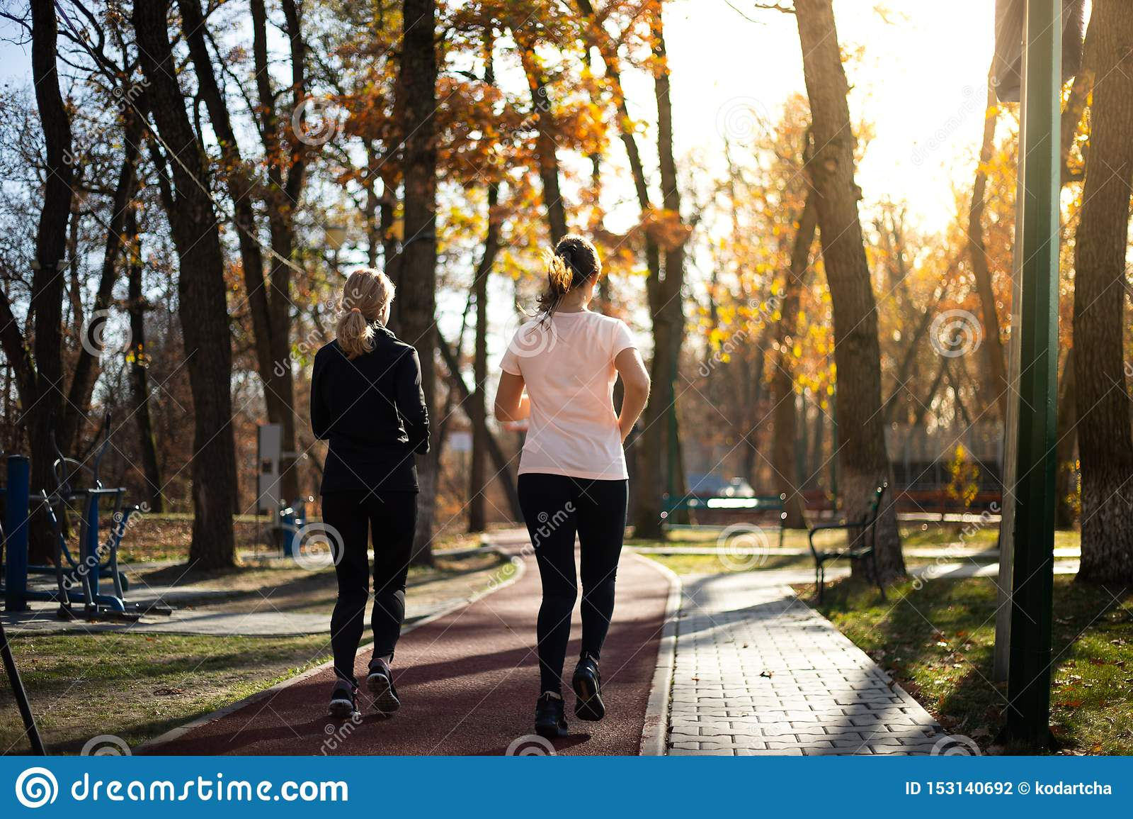 Duas mulheres aptas bonitas que correm nos parques durante a queda e os sóis