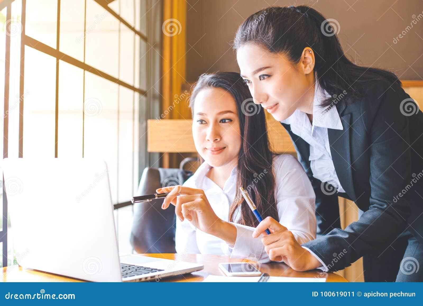 Duas mulheres de negócio estão trabalhando em um laptop, guardando a