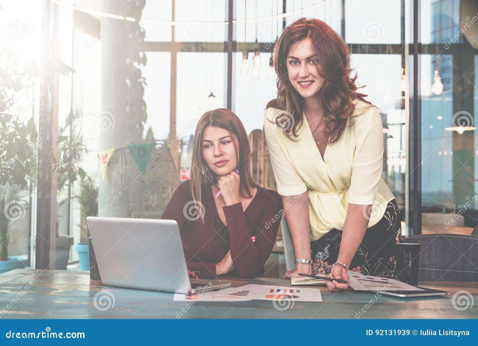 Duas mulheres de negócios novas estão trabalhando no escritório A primeira mulher senta-se na tabela e olha-se a tela do portátil