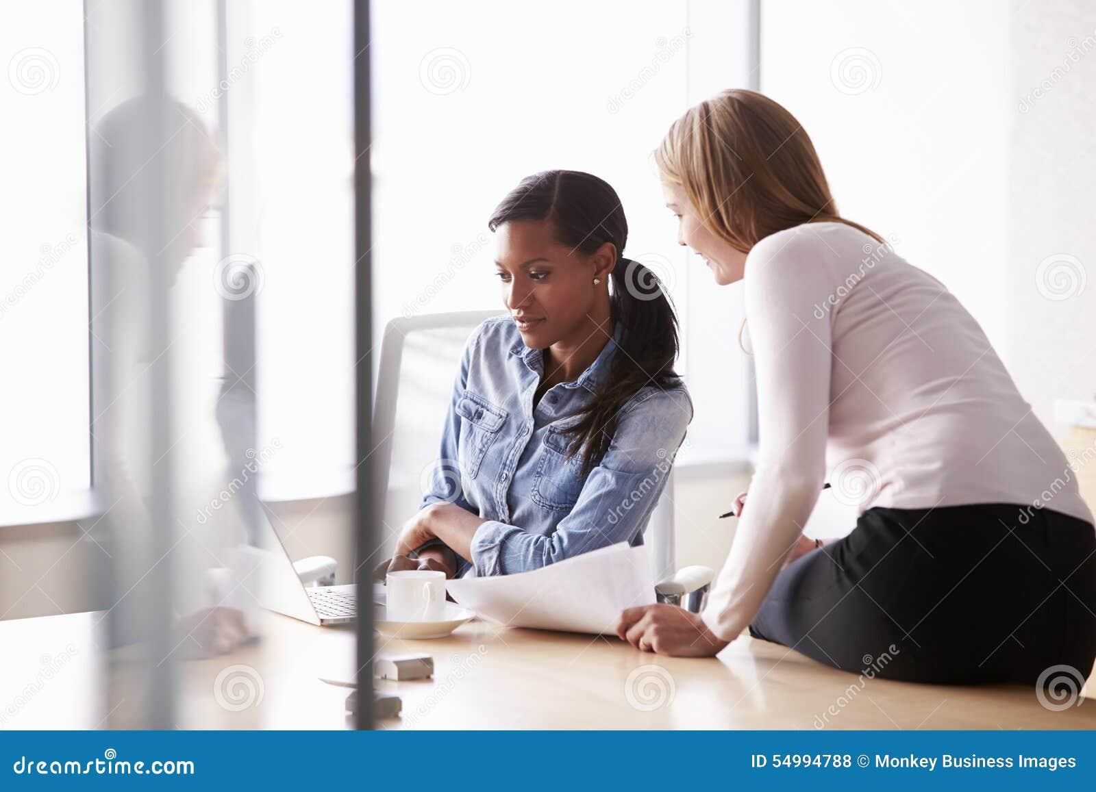 Duas mulheres de negócios ocasionalmente vestidas que trabalham no escritório