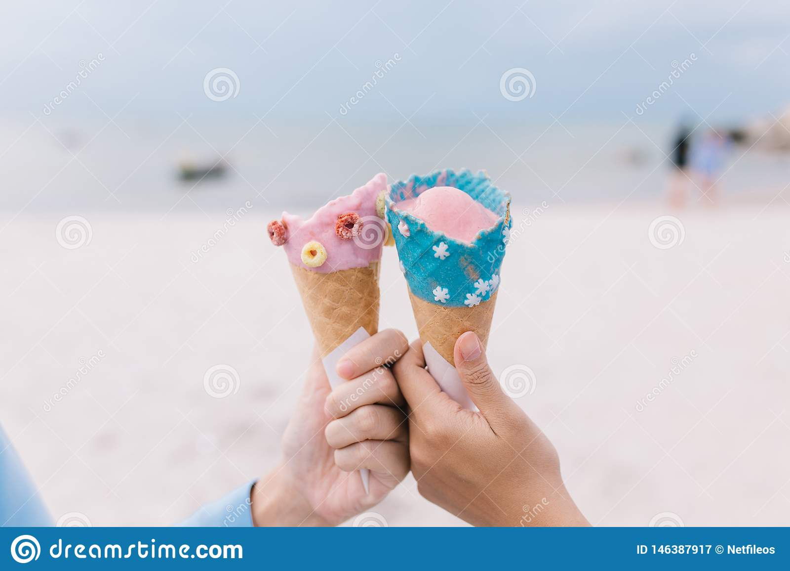 Duas mulheres do jovem adolescente das mãos que guardam o cone de gelado no verão na praia e no mar