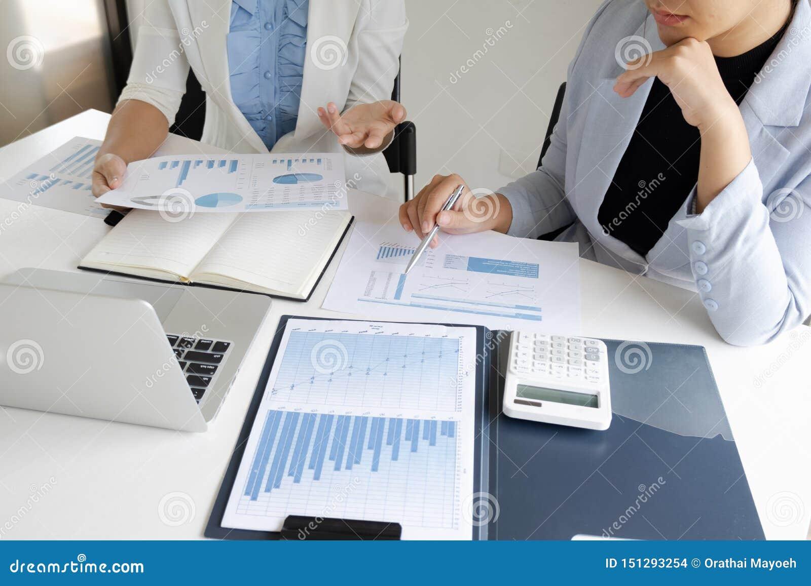 Duas mulheres do líder de negócio que discutem as cartas e os gráficos que mostram os resultados