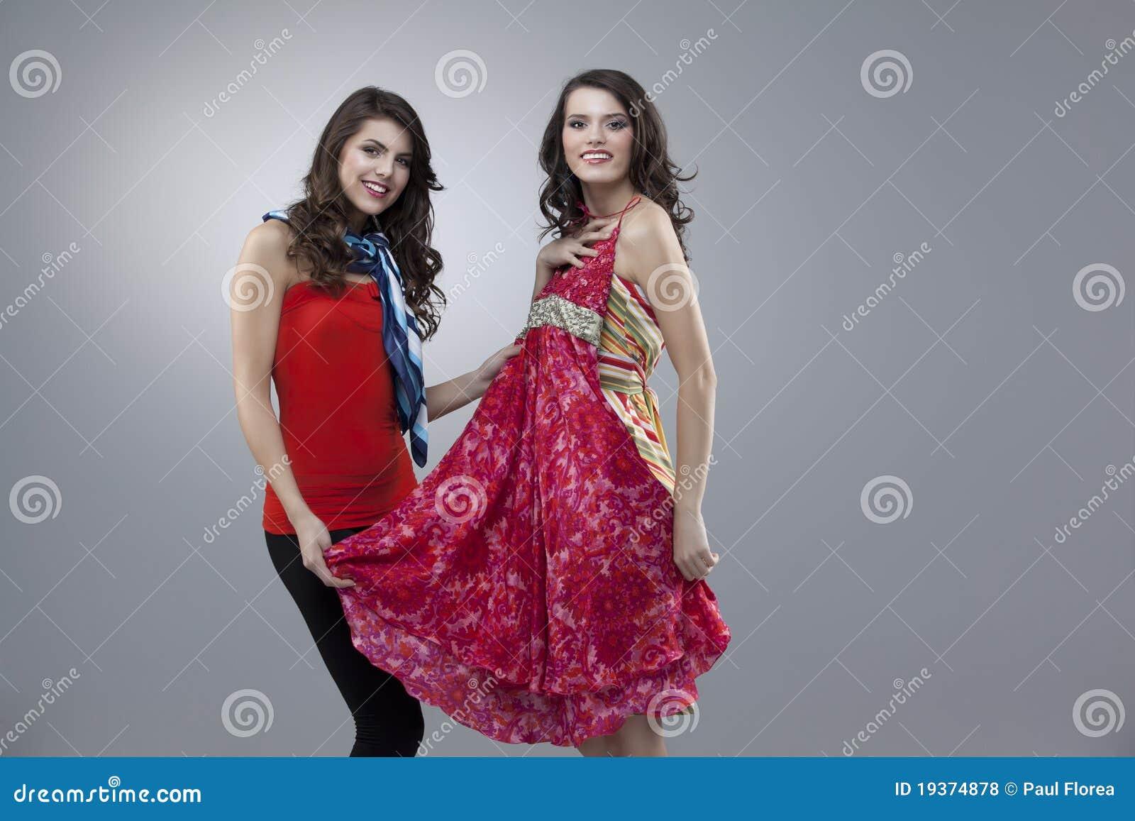 Duas mulheres felizes que tentam o vestido vermelho da flor
