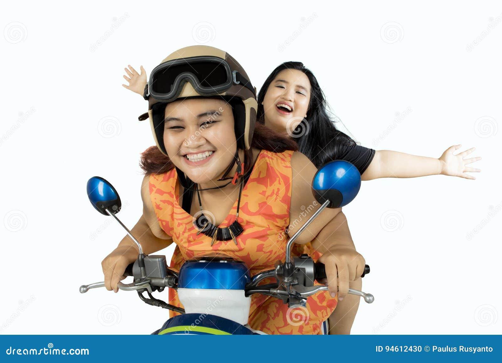 Duas mulheres gordas que conduzem a motocicleta junto