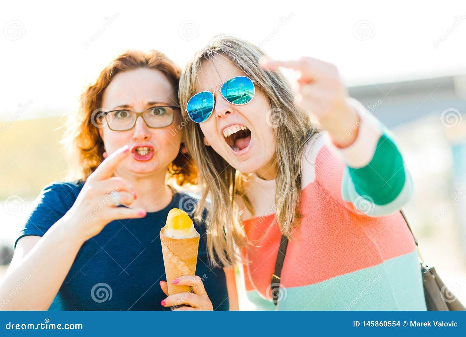 Duas mulheres irritadas que mostram gestos obscenos