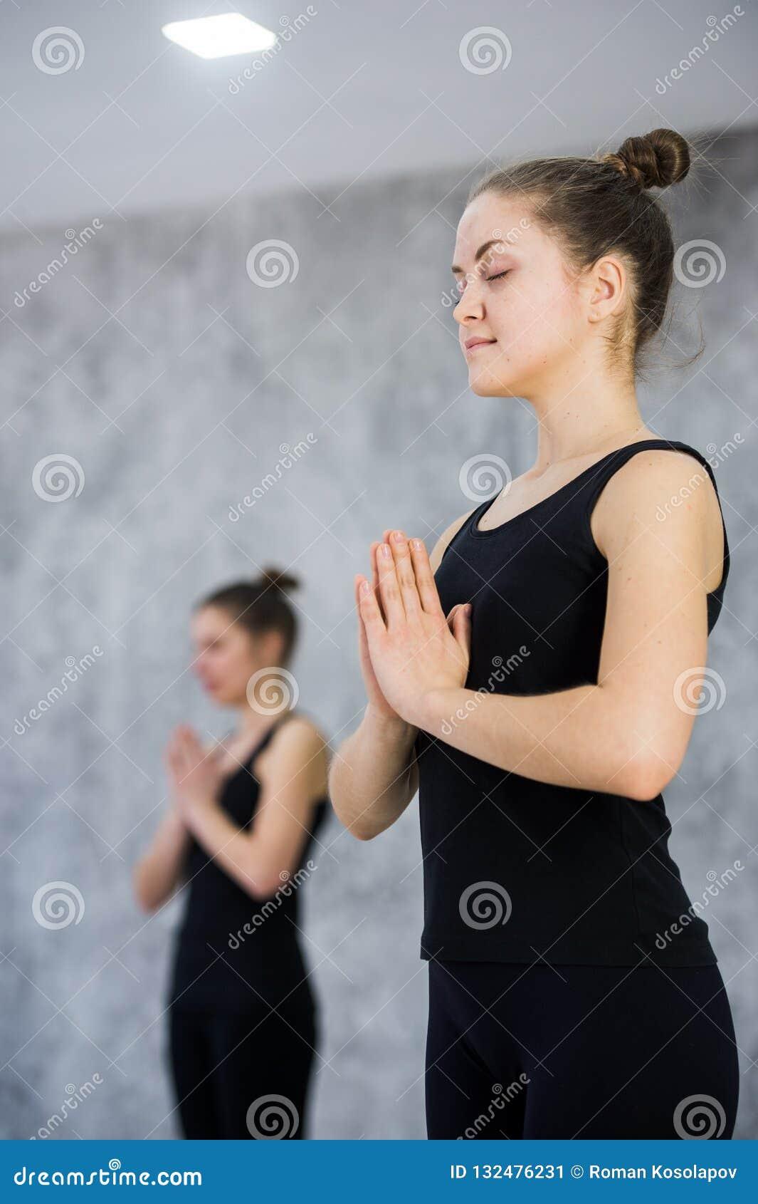Duas mulheres no gym classificam, exercício do abrandamento ou classe da ioga