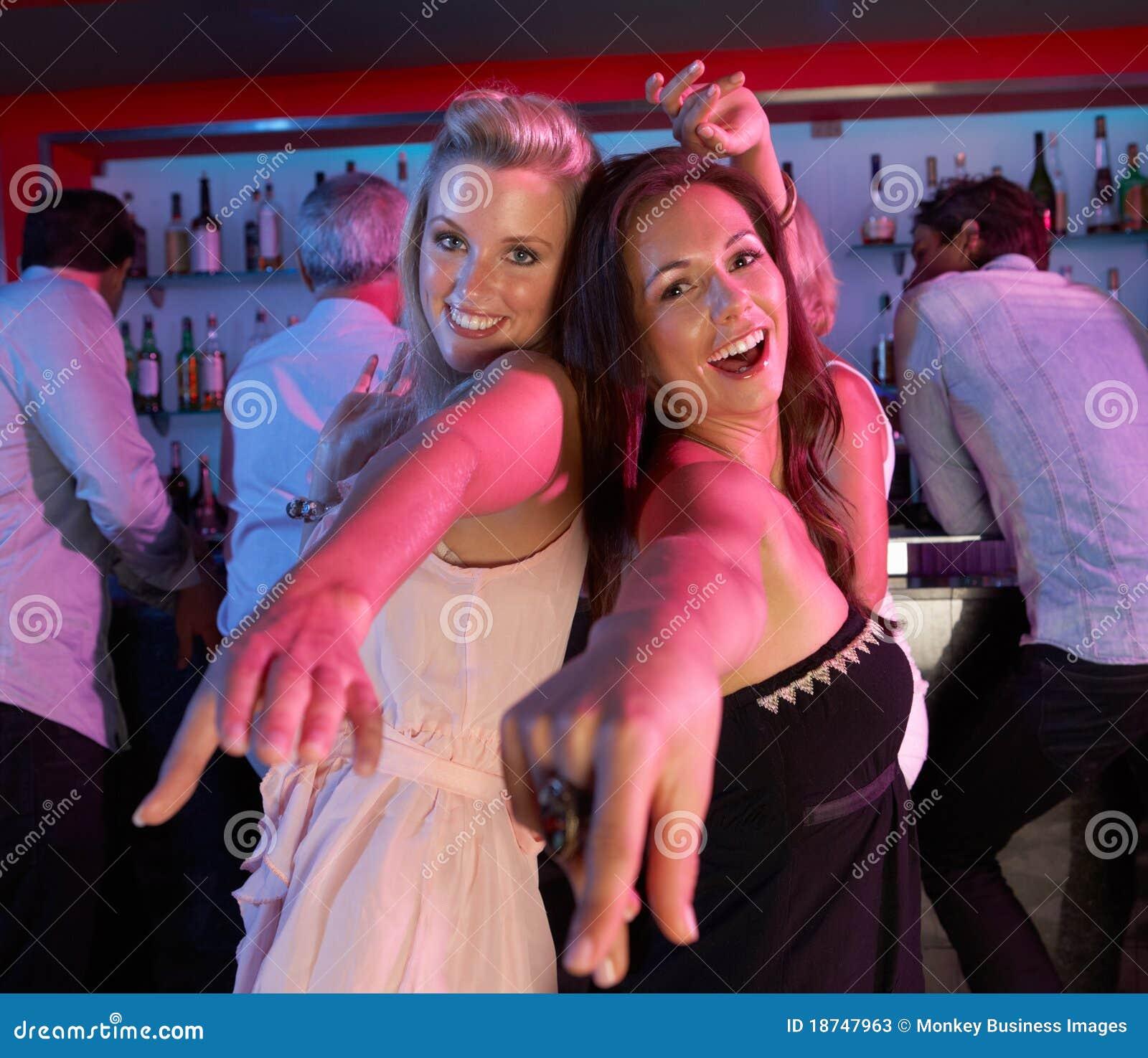 Duas mulheres novas que têm o divertimento na barra ocupada