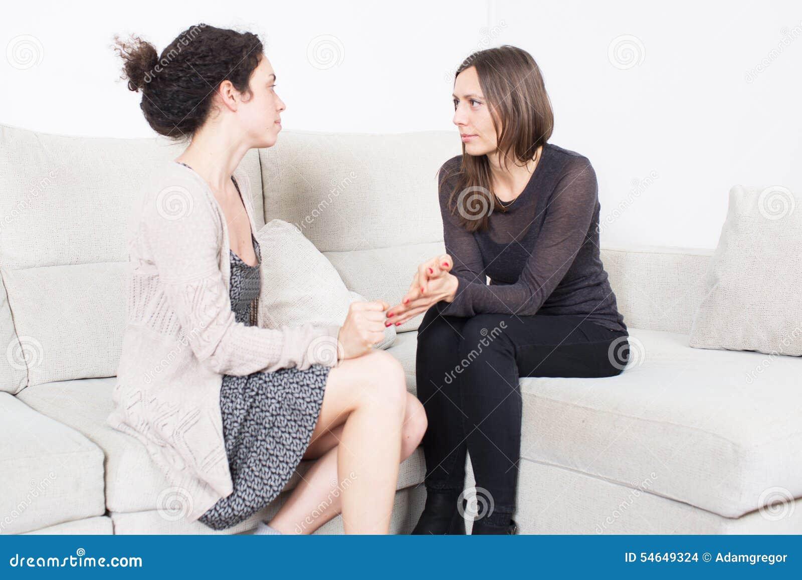 Duas mulheres que falam em um sofá