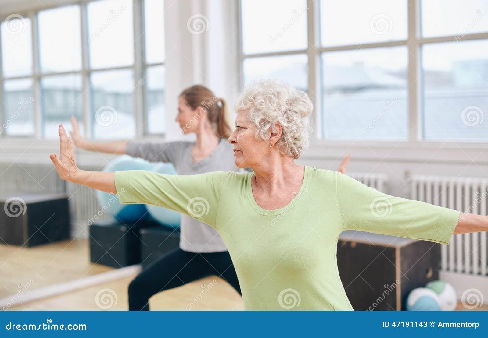 Duas mulheres que fazem o exercício da ioga no gym