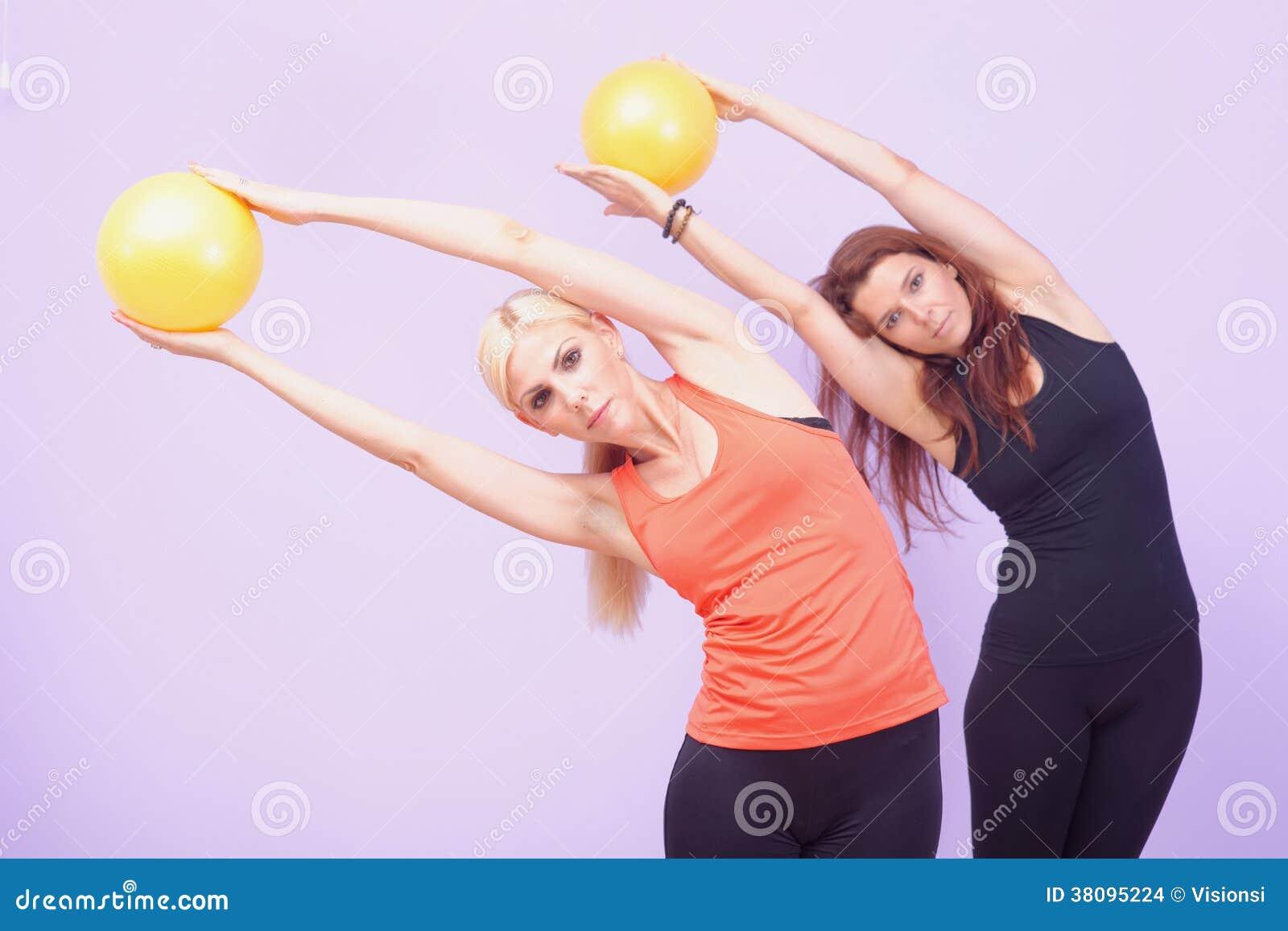 Duas mulheres que fazem o exercício de Pilates