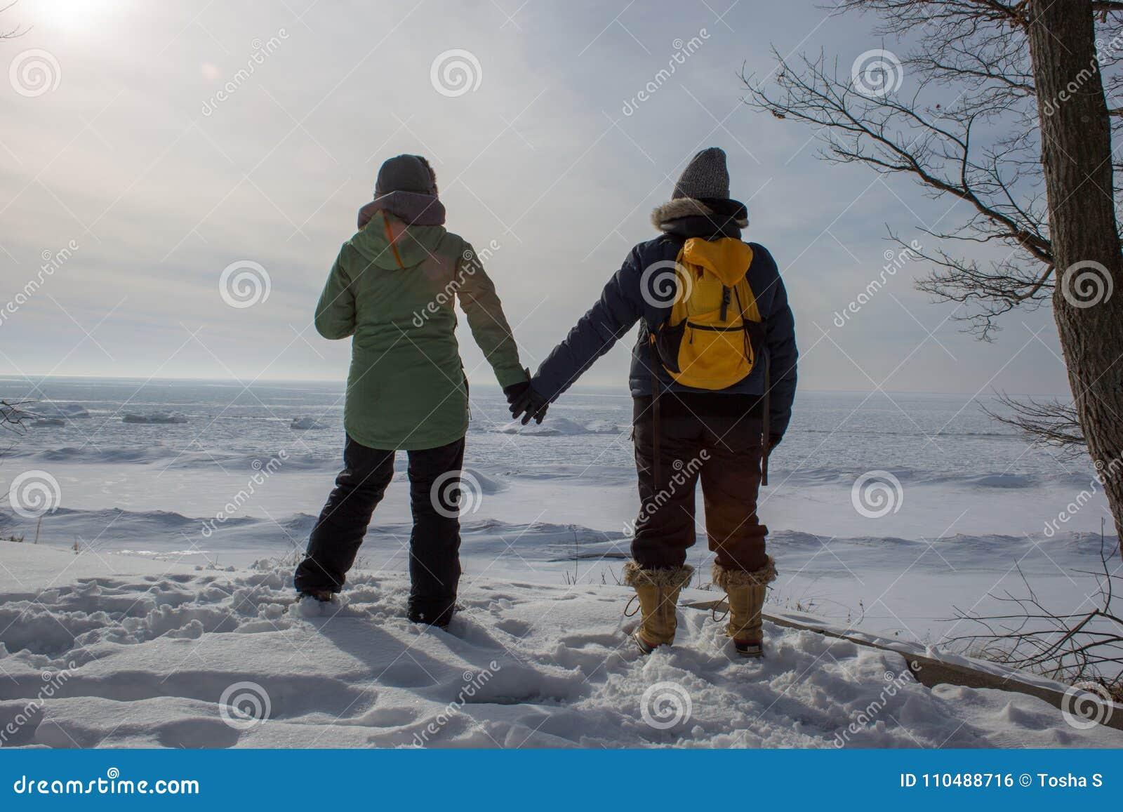 Duas mulheres que guardam as mãos em uma costa congelada do lago