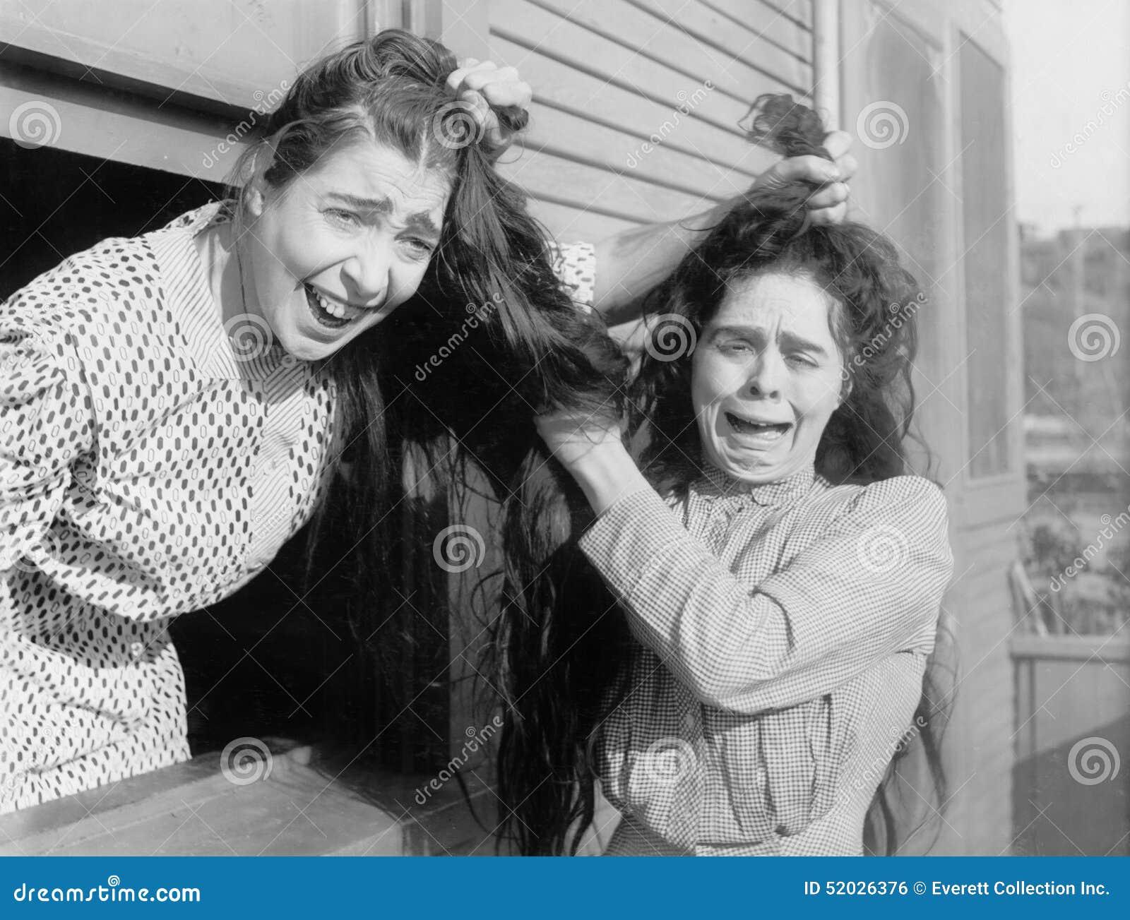 Duas mulheres que lutam e que puxam cada outro cabelo (todas as pessoas descritas não são umas vivas mais longo e nenhuma proprie