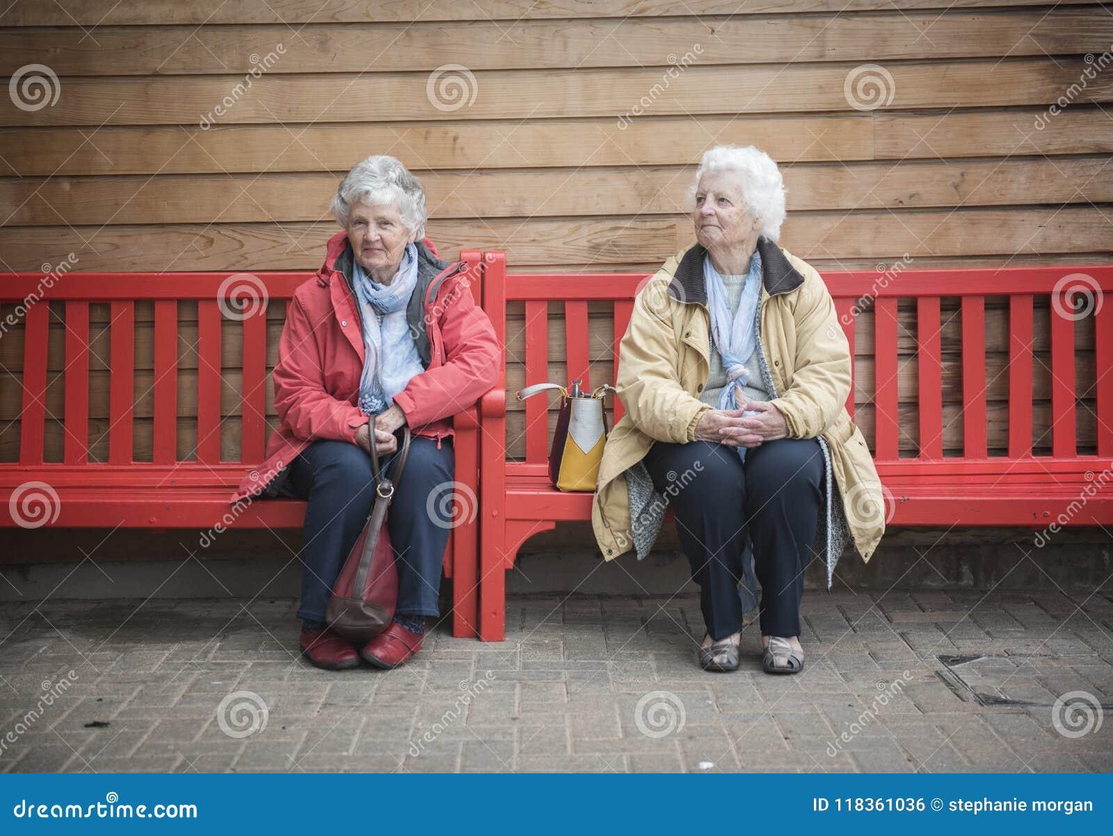 Duas mulheres superiores felizes que conversam em um banco vermelho fora