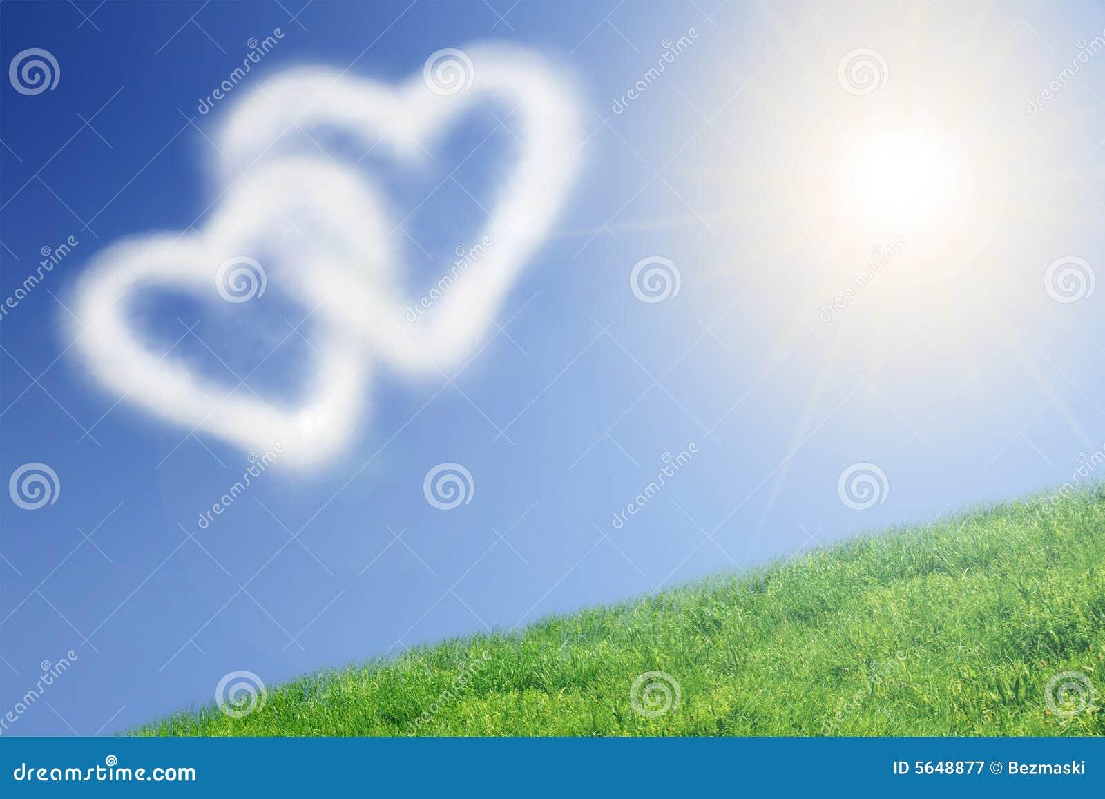 Duas nuvens heart-shaped e o sol